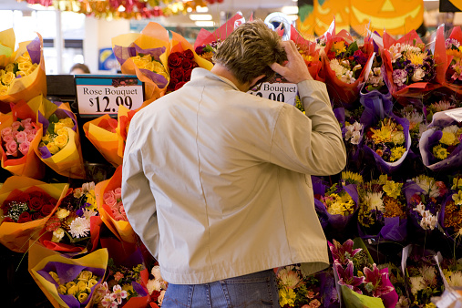 Man choosing bouquet of fresh flowers in grocery store